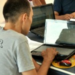Refugee strengthening computer skills through JRS education project.
