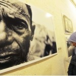 Visitor looking at the photo of a man blind in one eye after being beaten in the head during forced labor