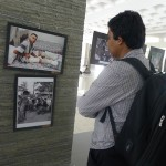 A student looking at the photos of cluster bomb survivals exhibited at Gadjah Mada University