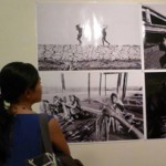 A visitor looking at photos of Greg Constantine at Jogja Gallery